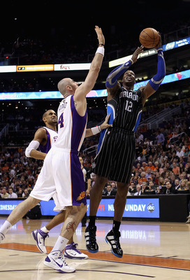 PHOENIX, AZ - MARCH 13:  Dwight Howard #12 of the Orlando Magic puts up a shot during the NBA game against the Phoenix Suns at US Airways Center on March 13, 2011 in Phoenix, Arizona. The Magic defeated the Suns 111-88. NOTE TO USER: User expressly acknow