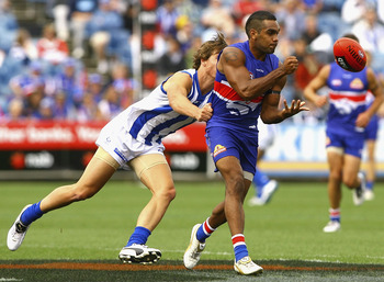 MELBOURNE, AUSTRALIA - FEBRUARY 20:  Nathan Djerrkura of the Bulldogs handballs under pressure during the Pool Six NAB Cup round one AFL match between the North Melbourne Kangaroos and the Western Bulldogs at Skilled Stadium on February 20, 2011 in Melbou