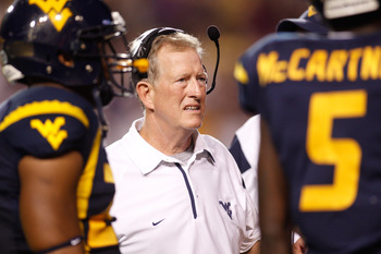 BATON ROUGE, LA - SEPTEMBER 25:  Head coach Bill Stewart of the West Virginia Mountaineers talks with his team during a timeout against the  Louisiana State University Tigers at Tiger Stadium on September 25, 2010 in Baton Rouge, Louisiana.  The Tigers de