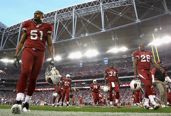 GLENDALE, AZ - DECEMBER 25:  (L-R) Paris Lenon #51, O'Brien Schofield #50, Deuce Lutui #76, Tim Hightower #34 and Beanie Wells #26 of the Arizona Cardinals walk off the field following warm ups to the NFL game against the Dallas Cowboys at the University