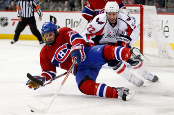 MONTREAL, CANADA - MARCH 15:  Mike Knuble #22 of the Washington Capitals takes down James Wisniewski #20 of the Montreal Canadiens during the NHL game at the Bell Centre on March 15, 2011 in Montreal, Quebec, Canada.  The Capitals defeated the Canadiens 4