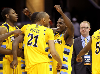 CLEVELAND, OH - MARCH 20: Joseph Fulce #21 and Darius Johnson-Odom #1 of the Marquette Golden Eagles celebrate with teammates after defeating the Syracuse Orange during the third of the 2011 NCAA men's basketball tournament at Quicken Loans Arena on March