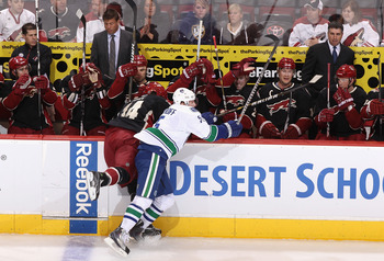 GLENDALE, AZ - MARCH 08:  Christian Ehrhoff #4 of the Vancouver Canucks lays a body check onto Taylor Pyatt #14 of the Phoenix Coyotes during the first period of the NHL game at Jobing.com Arena on March 8, 2011 in Glendale, Arizona.  (Photo by Christian