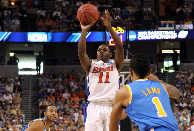 TAMPA, FL - MARCH 19:  Erving Walker #11 of the Florida Gators attempts a shot in the first half against the Tyler Lamb #1 of the UCLA Bruins during the third round of the 2011 NCAA men's basketball tournament at St. Pete Times Forum on March 19, 2011 in