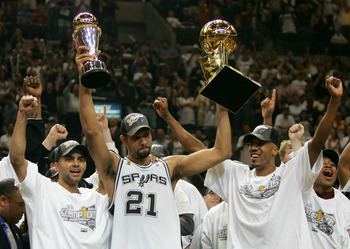 SAN ANTONIO - JUNE 23:  Tim Duncan #21, center, holds up the Finals MVP trophy and the Larry O'Brien trophy as teammates Tony Parker #9, left, and Bruce Bowen #12 of the San Antonio Spurs celebrate after defeating the Detroit Pistons in Game seven of the