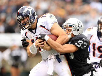 OAKLAND, CA - DECEMBER 19:  Tim Tebow #15 of the Denver Broncos gets past Tyvon Branch #33 of the Oakland Raiders to score a touchdown at Oakland-Alameda County Coliseum on December 19, 2010 in Oakland, California.  (Photo by Ezra Shaw/Getty Images)