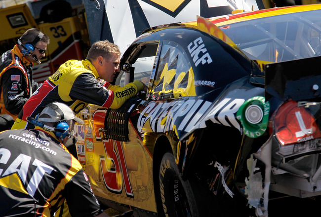 AVONDALE, AZ - FEBRUARY 27:  Clint Bowyer, driver of the #33 Cheerios Chevrolet, talks to Jeff Burton, driver of the #31 Caterpilliar Chevrolet, in the garage after both were involved in a crash during the NASCAR Sprint Cup Series Subway Fresh Fit 500 at