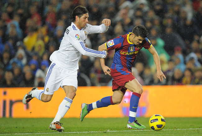 BARCELONA, SPAIN - NOVEMBER 29:  David Villa of Barcelona (R) vies for the ball with Sergio Ramos of Real Madrid during the La Liga match between Barcelona and Real Madrid at the Camp Nou Stadium on November 29, 2010 in Barcelona, Spain.  Barcelona won th