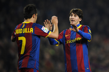BARCELONA, SPAIN - FEBRUARY 05:  Lionel Messi of Barcelona (R) celebrates with his teammate David Villa after scoring his third goal during the La Liga match between Barcelona and Atletico de Madrid at Camp Nou on February 5, 2011 in Barcelona, Spain.  (P