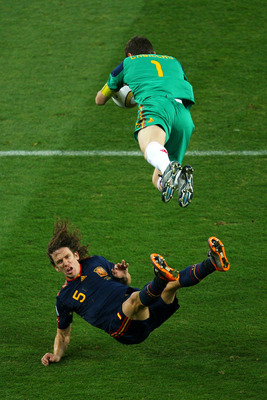 JOHANNESBURG, SOUTH AFRICA - JULY 11:  Iker Casillas of Spain catches the ball and falls over team mate Carles Puyol during the 2010 FIFA World Cup South Africa Final match between Netherlands and Spain at Soccer City Stadium on July 11, 2010 in Johannesb