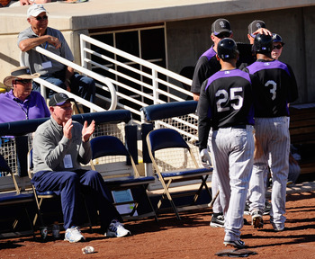 PHOENIX, AZ - MARCH 10:  George Karl (L) coach of the Denver Nuggets looks on as managerJim Tracy of the Colorado Rockies congratulates Carlos Gonzalez #25 and and Willy Taveras #3 after they scored on teammate Todd Helton's two-run double against the Mil