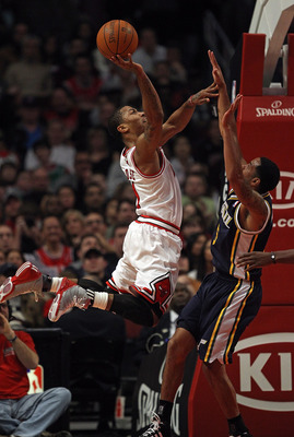 CHICAGO, IL - MARCH 12: Derrick Rose #1 of the Chicago Bulls puts up a shot over Devin Harris #5 of the Utah Jazz at the United Center on March 12, 2011 in Chicago, Illinois. The Bulls defeated the Jazz 118-100. NOTE TO USER: User expressly acknowledges a