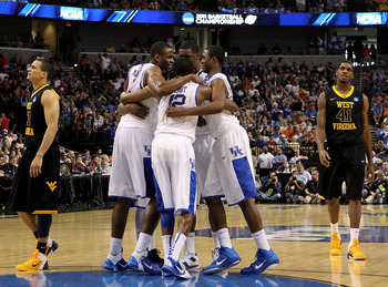 TAMPA, FL - MARCH 19:  Brandon Knight #12 of the Kentucky Wildcats huddles up with his teammates against as Joe Mazzulla #21 and John Flowers #41 of the West Virginia Mountaineers look on during the third round of the 2011 NCAA men's basketball tournament