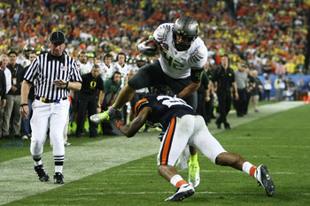 GLENDALE, AZ - JANUARY 10:  David Paulson #42 of the Oregon Ducks is upended as he tries to avoid the tackle of Mike McNeil #26 of the Auburn Tigers during the Tostitos BCS National Championship Game at University of Phoenix Stadium on January 10, 2011 in