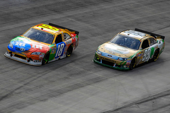 BRISTOL, TN - MARCH 20:  Kyle Busch, driver of the #18 M&M'sToyota, leads Carl Edwards, driver of the #99 Aflac Ford, during the NASCAR Sprint Cup Series Jeff Byrd 500 Presented By Food City at Bristol Motor Speedway on March 20, 2011 in Bristol, Tennesse