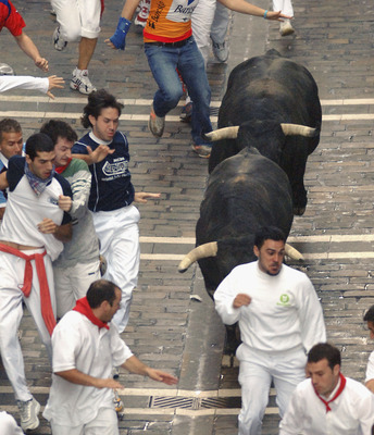 PAMPLONA, SPAIN - JULY 12: People try to evade Juan pedro Domecq running bulls on the sixth day of the San Fermin Fiesta on July 12, 2005 in Pamplona, Spain. The 'Encierro' or running of the bulls dates back to the 14th century when bulls were herded down