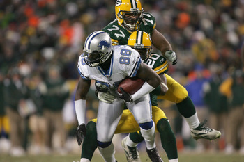 GREEN BAY, WI -DECEMBER 11: Mike Williams #88 of the Detroit Lions grips the ball as he is tackled by Mark Roman #20 and Cullen Jenkins #77 of the Green Bay Packers during the game against the Detroit Lions on December 11, 2005 at Lambeau Field in Green B