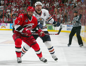 RALEIGH, NC - JUNE 19:  Niclas Wallin #7 of the Carolina Hurricanes holds off Ethan Moreau #18 of the Edmonton Oilers during game seven of the 2006 NHL Stanley Cup Finals on June 19, 2006 at the RBC Center in Raleigh, North Carolina. The Hurricanes defeat