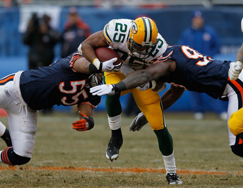 CHICAGO - DECEMBER 13: Ryan Grant #25 of the Green Bay Packers tries to break away from Lance Briggs #55 and Gaines Adams #99 of the Chicago Bears at Soldier Field on December 13, 2009 in Chicago, Illinois. The Packers defeated the Bears 21-14. (Photo by