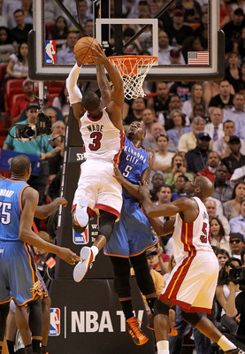 MIAMI, FL - MARCH 16:  Dwyane Wade #3 of the Miami Heat dunks over Kendrick Perkins #5 of the Oklahoma City Thunder during a game at American Airlines Arena on March 16, 2011 in Miami, Florida. NOTE TO USER: User expressly acknowledges and agrees that, by