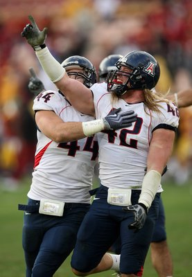 LOS ANGELES, CA - DECEMBER 05:  Defensive ends Brooks Reed #42 and Ricky Elmore #44 of the Arizona Wildcats celebrate after stopping the USC Trojans on the final play on December 5, 2009 at the Los Angeles Coliseum in Los Angeles, California. Arizona won