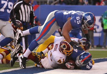 EAST RUTHERFORD, NJ - DECEMBER 05:  Ahmad Bradshaw #44 of the New York Giants scores a touchdown against Kareem Moore #41 of the Washington Redskins as Will Beatty #65 leaps over the pile during their game on December 5, 2010 at The New Meadowlands Stadiu
