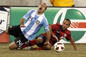 EAST RUTHERFORD, NJ - MARCH 26:  Javier Mascherano #14 of Argentina falls to the turf on front of Landon Donovan #10 of the United States during the second half of a friendly match at New Meadowlands Stadium on March 26, 2011 in East Rutherford, New Jerse
