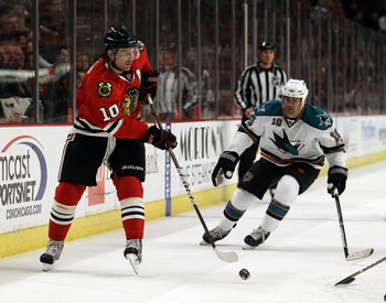 CHICAGO, IL - MARCH 14: Patrick Sharp #10 of the Chicago Blackhawks passes the puck in front of Jamal Mayers #10 of the San Jose Sharks at the United Center on March 14, 2011 in Chicago, Illinois. The Blackhawks defeated the Sharks 6-3. (Photo by Jonathan