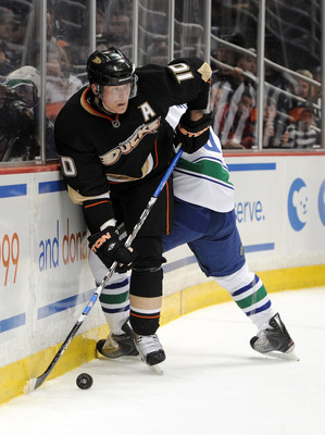 ANAHEIM, CA - MARCH 06:  Corey Perry #10 of the Anaheim Ducks looks to pass as he is pinned to the boards by Christian Ehrhoff #5 of the Vancouver Canucks during the first period at the Honda Center on March 6, 2011 in Anaheim, California.  (Photo by Harr