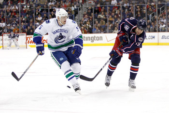 COLUMBUS, OH - DECEMBER 23:  Ethan Moreau #19 of the Columbus Blue Jackets shoots the puck past Christian Ehrhoff #5 of the Vancouver Canucks during the second period on December 23, 2010 at Nationwide Arena in Columbus, Ohio.  (Photo by John Grieshop/Get