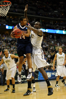 DENVER, CO - MARCH 17:  Kevin Anderson #14 of the Richmond Spiders handles the ball against Steve Tchiengang #33 of the Vanderbilt Commodores during the second round of the 2011 NCAA men's basketball tournament at Pepsi Center on March 17, 2011 in Denver,