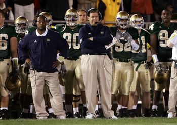 SOUTH BEND, IN - OCTOBER 15:  Head coach Charlie Weis of the Notre Dame Fighting Irish (C) watches the end of a game against the University of Southern California Trojans with assistant Mike Haywood (L) on October 15, 2005 at Notre Dame Stadium in South B