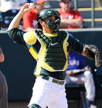 PHOENIX, AZ - MARCH 04:  Kurt Suzuki #8 of the Oakland Athletics throws the ball back to the pitcher against the Texas Rangers at Phoenix Municipal Stadium on March 4, 2011 in Phoenix, Arizona.  (Photo by Norm Hall/Getty Images)