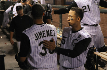 DENVER - SEPTEMBER 27:  Starting pitcher Ubaldo Jimenez #38 of the Colorado Rockies is welcomed back to the dugout by Carlos Gonzalez #5 after a successful sacrifice bunt against the Los Angeles Dodgers at Coors Field on September 25, 2010 in Denver, Colo