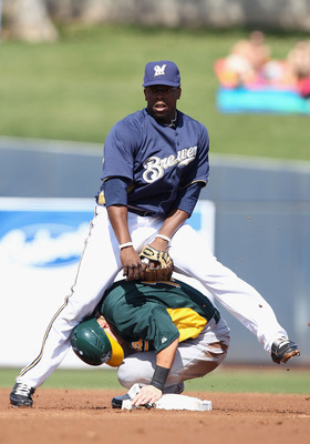 PHOENIX, AZ - MARCH 03:  Infielder Rickie Weeks #23 of the Milwaukee Brewers stands over Daric Barton #10 of the Oakland Athletics after completing a double play during the first inning of the spring training game at Maryvale Baseball Park on March 3, 201