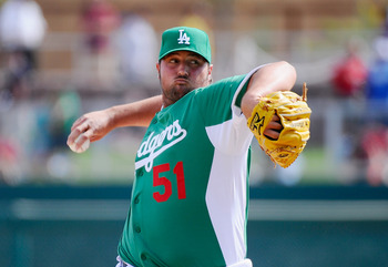 GLENDALE, AZ - MARCH 17:  Pitcher Jonathan Broxton #51 of the Los Angeles Dodgers wearing a green jersey in celebration of St. Patrick's Day throws a pitch against the Arizona Diamondbacks during the spring training baseball game on March 17, 2011 in Glen