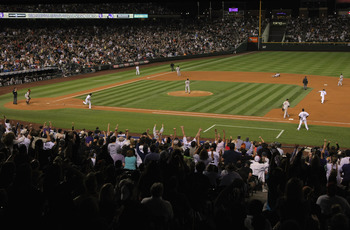 DENVER - SEPTEMBER 25:  The crowd errupts as Troy Tulowitzki #2 of the Colorado Rockies doubles past shortstop Juan Uribe #5 of the San Francisco Giants to score Carlos Gonzalez for the game winning run in the 10th inning at Coors Field on September 25, 2
