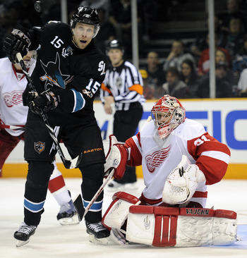 SAN JOSE, CA - MARCH 3: Dany Heatley #15 of the San Jose Sharks deflects the puck in front of goalie Joey MacDonald #31 of the Detroit Red Wings in the second period of an NHL hockey game at the HP Pavilion on March 3, 2011 in San Jose, California. The Sh