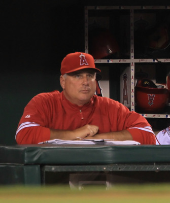 ANAHEIM, CA - SEPTEMBER 07:  Hideki Matsuil #55 of the Los Angeles Angels of Anaheim looks on from the dugout alongside manager Mike Scioscia after being forced out at second base in the seventh inning against the Cleveland Indians at Angel Stadium on Sep