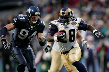 SEATTLE - JANUARY 8:  Running back Marshall Faulk #28 of the St. Louis Rams runs away from linebacker Chad Brown #94 of the Seattle Seahawks in the NFC wild-card game at Qwest Field on January 8, 2005 in Seattle, Washington. The Rams defeated the Seahawks