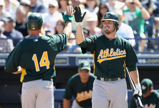 PEORIA, AZ - MARCH 12:  Mark Ellis #14 of the Oakland Athletics high fives teammate Andy LaRoche #21 after Ellis scored a run against the Seattle Mariners during the second inning of the spring training game at Peoria Stadium on March 12, 2011 in Peoria,
