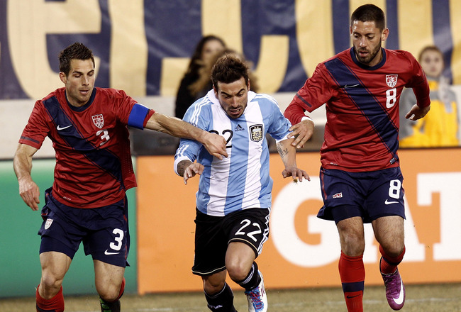 EAST RUTHERFORD, NJ - MARCH 26:  Ezequiel Lavezzi #22 of Argentina dribbles between Carlos Bocanegra #3 and Clint Dempsey #8 of the United States during the first half of a friendly match at New Meadowlands Stadium on March 26, 2011 in East Rutherford, Ne
