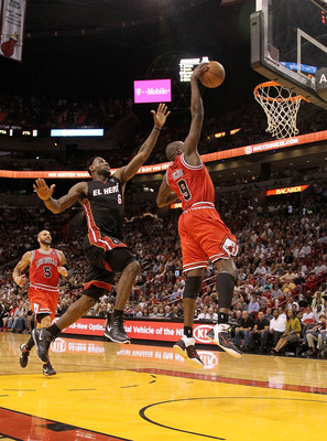 MIAMI, FL - MARCH 06:  Luol Deng #9 of the Chicago Bulls dunks past LeBron James #6 of the Miami Heat during a game at American Airlines Arena on March 6, 2011 in Miami, Florida. NOTE TO USER: User expressly acknowledges and agrees that, by downloading an