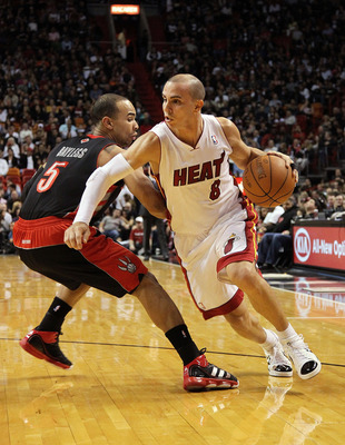 MIAMI, FL - JANUARY 22:  Carlos Arroyo #8 of the Miami Heat dribbles by Jerryd Bayless #5 of the Toronto Raptors during a game at American Airlines Arena on January 22, 2011 in Miami, Florida. NOTE TO USER: User expressly acknowledges and agrees that, by