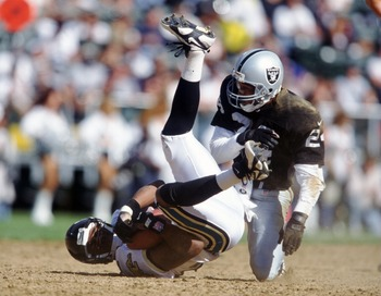 15 Sep 1996:  Defensive back Larry Brown #24 of the Oakland Raiders puts a hit on receiver Jimmy Smith of the Jacksonville Jaguars during the Raiders 17-3 win at the Oakland Coliseum in Oakland, California. Mandatory Credit: Stephen Dunn/ALLSPORT