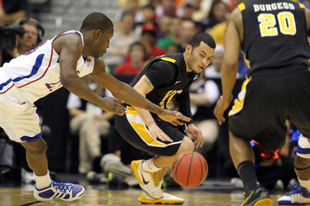 SAN ANTONIO, TX - MARCH 27:  Joey Rodriguez #12 of the Virginia Commonwealth Rams and Mario Little #23 of the Kansas Jayhawks go for the loose ball during the southwest regional final of the 2011 NCAA men's basketball tournament at the Alamodome on March