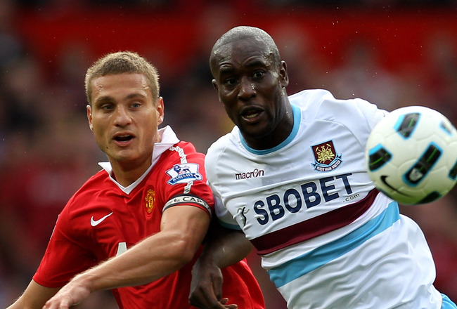 MANCHESTER, ENGLAND - AUGUST 28:  Carlton Cole of West Ham United tangles with Nemanja Vidic of Manchester United during the Barclays Premier League match between Manchester United and West Ham United at Old Trafford on August 28, 2010 in Manchester, Engl