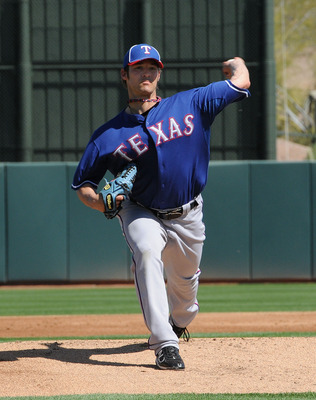 PHOENIX, AZ - MARCH 04:  C.J. Wilson #36 of the Texas Rangers delivers a pitch against the Oakland Athletics at Phoenix Municipal Stadium on March 4, 2011 in Phoenix, Arizona.  (Photo by Norm Hall/Getty Images)