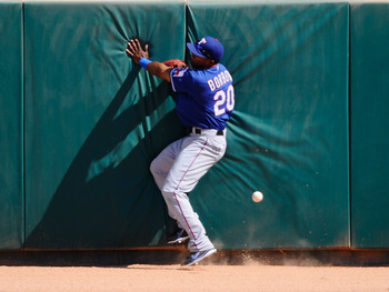 GLENDALE, AZ - MARCH 15:  Julio Borbon #20 of the Texas Rangers crashes against the center field wall as he chases a two-run triple by Juan Uribe #5 of the Los Angeles Dodgers that scored Ivan DeJesus #65 and Andre Ethier #16 during the thrid inning of th