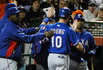 SCOTTSDALE, AZ - MARCH 07:  Michael Young #10 of the Texas Rangers is congratulated by manager Ron Washington (L) after scoring a run on a double by teammate Yorvit Torrealba in the first inning against the San Francisco Giants in the first meeting betwee